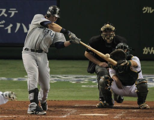 Seattle Mariners' Justin Smoak hits a solo homer in front of Oakland Athletics catcher Kurt Suzuki in the seventh inning of their American League MLB baseball game at Tokyo Dome in Tokyo,Thursday, Mar 29, 2012. (AP Photo/Itsuo Inouye)