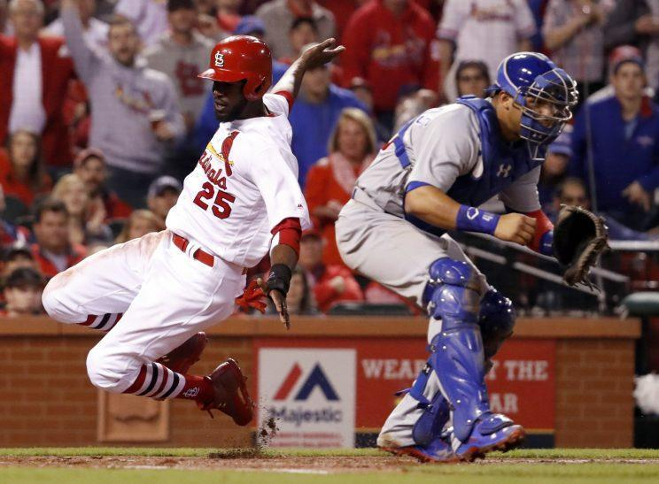St. Louis Cardinals' Dexter Fowler, left, scores past Chicago Cubs catcher Willson Contreras during the third inning of a baseball game Sunday, April 2, 2017, in St. Louis. (AP Photo/Jeff Roberson)s