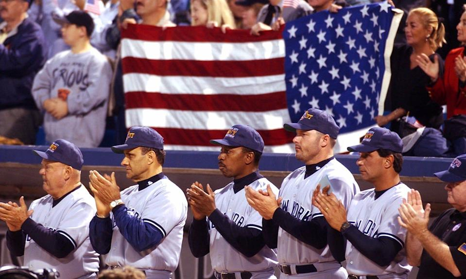 Yankees manager Joe Torre, second from left, claps as Chicago firemen and police officers walk to the pitchers mound in Chicago in the first game following the 9/11 attacks.