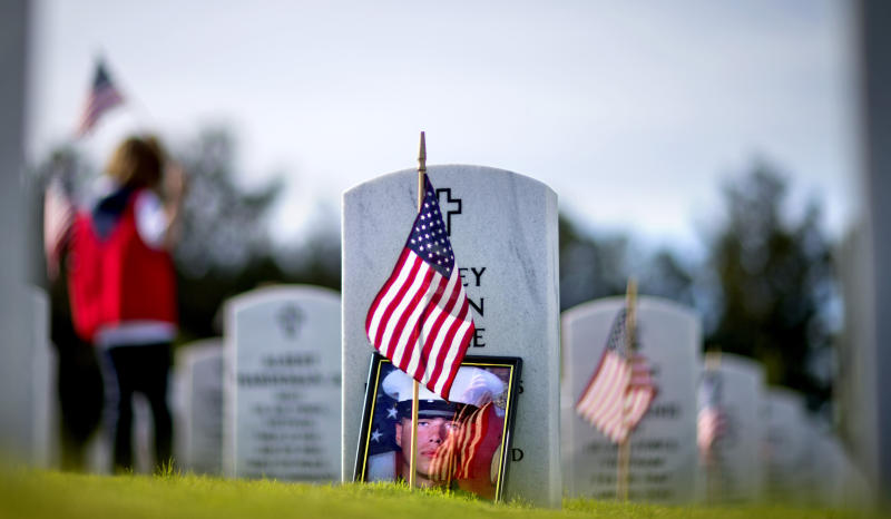 A photo of U.S. Marine Lance Cpl. Corey Allen Little leans against his tombstone as volunteers place American flags at the graves of military service members at Georgia National Cemetery before the Memorial Day holiday, Saturday, May 25, 2013, in Canton, Ga. Little, 25, who was expecting his first child, was one of seven Marines who died in a helicopter crash Feb. 22, 2012, while training for a deployment to Afghanistan. (AP Photo/David Goldman)