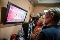 Indonesian locals watch a television showing live news of Indonesian President Joko Widodo receiving his COVID-19 vaccine shot in Jakarta, Indonesia