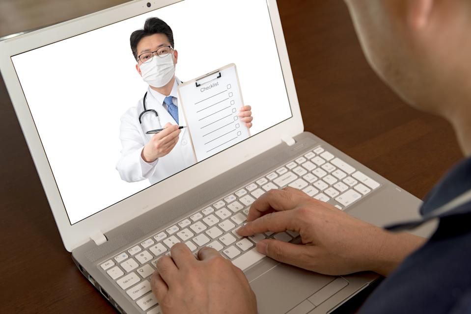 an Asian doctor who is remotely consulting with a patient. Telehealth concept.  The person on the screen is the same person.
