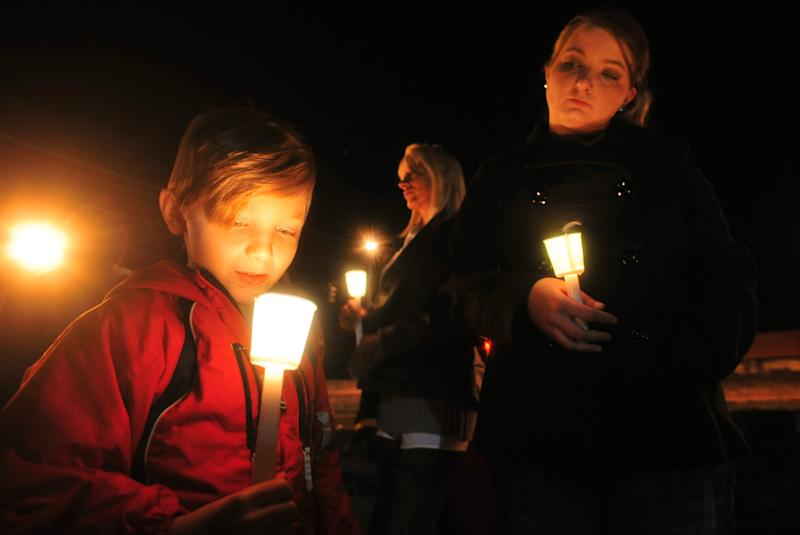 Cade Smith, 6, watches the flame of his candle burn as his mother, Brandi, looks on during a candlelight vigil for the families involved in the ongoing hostage crisis Friday night, Feb. 1, 2013 in Midland City, Ala. The Smith family feels a connection to the autistic boy named Ethan being held hostage because their son, Cade, also has autism. (AP Photo/The Dothan Eagle, Jay Hare)