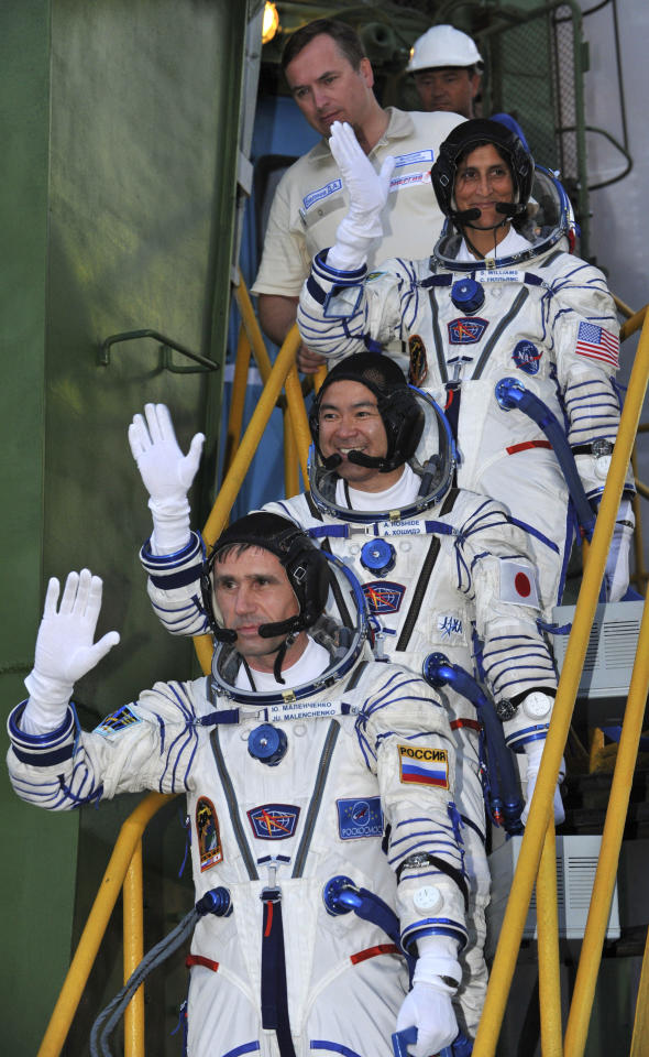 Russian cosmonaut Yuri Malenchenko, center, U.S. astronaut Sunita Williams, above, and Japanese astronaut Akihiko Hoshide, crew members of the mission to the International Space Station, ISS, gesture prior to the launch of the Soyuz-FG rocket at the Russian leased Baikonur Cosmodrome, in Kazakhstan, Sunday, July 15, 2012. (AP Photo/Vyacheslav Oseledko, Pool)