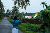 A man takes pictures with his mobile phone near the wreckage of an Air India Express jet at Calicut International Airport in Karipur, Kerala, on August 8, 2020. - Fierce rain and winds lashed a plane carrying 190 people before it crash-landed and tore in two at an airport in southern India, killing at least 19 people and injuring scores more, officials said on August 8. (Photo by Arunchandra BOSE / AFP) (Photo by ARUNCHANDRA BOSE/AFP via Getty Images)