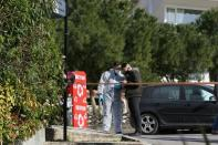 Forensic experts are seen on the road where Greek journalist George Karaivaz was fatally shot in the Alimos suburb of Athens