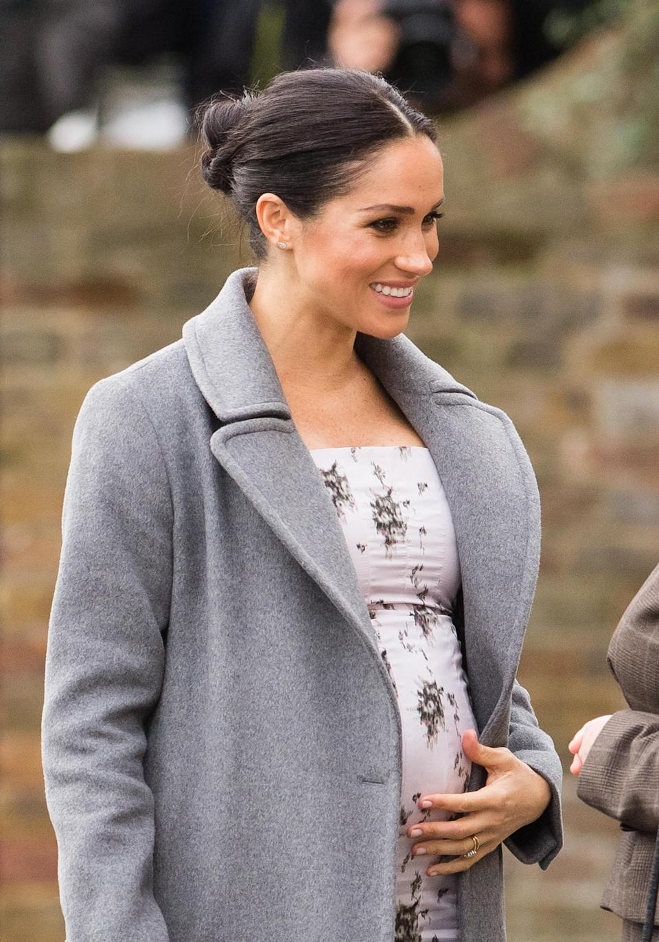 Meghan pats her baby bump [Photo: Getty]