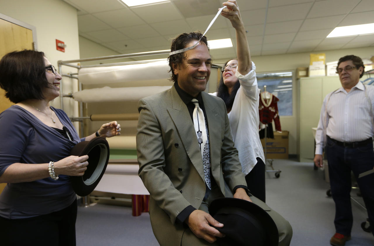 "Former MLB baseball player Mike Piazza is fitted for his costume by Maria Morales for his role in ""Slaughter on Tenth Avenue"" at the Miami City Ballet, as costume designer Haydee Morales, looks on at left, Tuesday, April 16, 2013, in Miami Beach, Fla. Piazza will play a gangster in the ballet on May 3. He will say a few lines and then watch the rest of the performance from a seat onstage. Piazza says his turn with the troupe is his gift to his 6-year-old daughter, a student at Miami City Ballet School. (AP Photo/Lynne Sladky)"