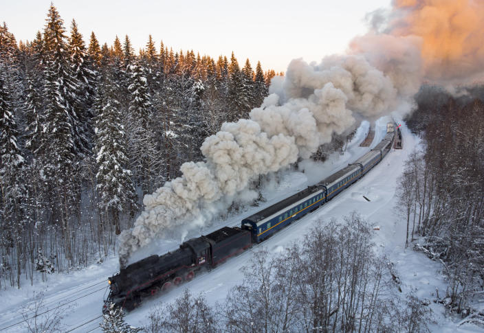 A Soviet-era steam locomotive pulls a retro train taking tourists to the Ruskeala natural park from the city of Sortavala, Karelia region, Russia. Russia's rollout of its coronavirus vaccine is only now picking up speed in some of its more remote regions. The experts blame the slow rollout on limited supplies of the vaccine, logistical difficulties in distribution and continued hesitance among some Russians. (AP Photo/Dmitri Lovetsky, File)