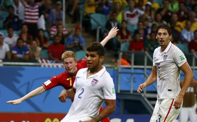 Belgium's Kevin De Bruyne runs past DeAndre Yedlin (2) and Omar Gonzalez of the U.S. to celebrate after scoring his goal during extra time in their 2014 World Cup round of 16 game at the Fonte Nova arena in Salvador July 1, 2014. REUTERS/Michael Dalder (BRAZIL - Tags: TPX IMAGES OF THE DAY SOCCER SPORT WORLD CUP)