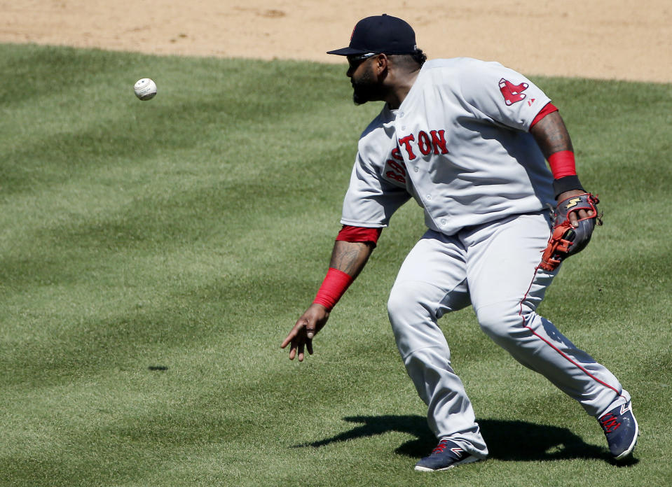 Boston Red Sox third baseman Pablo Sandoval mishandles the ball while attempting to throw to first during the third inning of a baseball game against the Texas Rangers, Sunday, May 31, 2015, in Arlington, Texas. Andrus was safe on the play. (AP Photo/Brandon Wade)