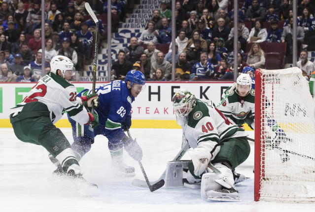 Vancouver Canucks' Jay Beagle (83) scores against Minnesota Wild goalie Devan Dubnyk (40) as Kevin Fiala, left, of Switzerland, watches during the second period of an NHL hockey game Wednesday, Feb. 19, 2020, in Vancouver, British Columbia. (Darryl Dyck/The Canadian Press via AP)