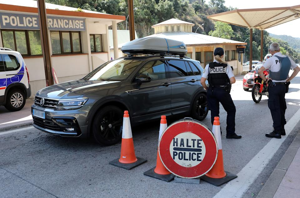 French police officers control vehicles at the border point with Spain, in Le Perthus, southern France on July 25, 2020. - French Prime Minister on July 24 said that while France's border with Spain would remain open for now despite a surge in cases in Catalonia, French people should avoid going there until the health situation improves. (Photo by RAYMOND ROIG / AFP) (Photo by RAYMOND ROIG/AFP via Getty Images)