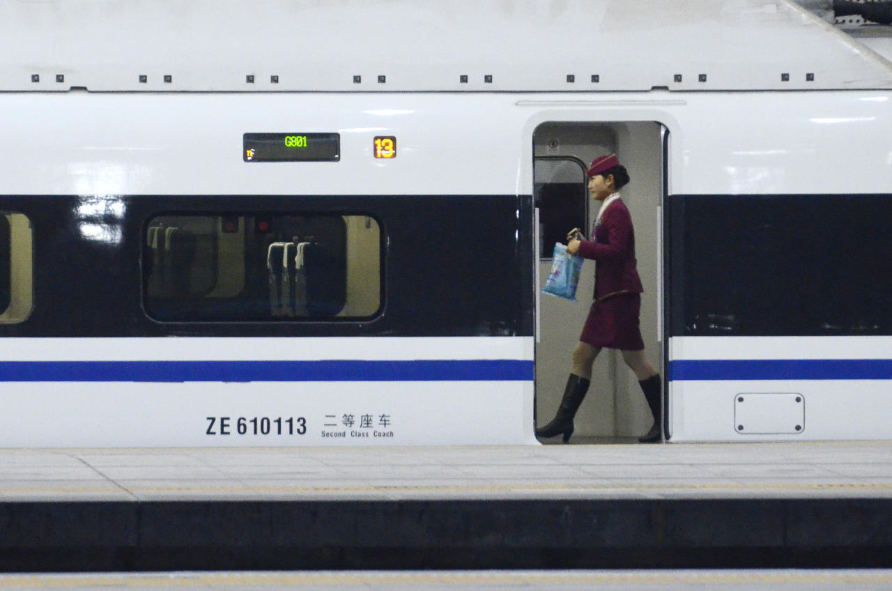 TOPSHOTS  A stewardess walks inside a high-speed train running from the Beijing to Guangzhou, south China's Guangdong province, at the Beijing west railway station in Beijing on December 26, 2012. China on December 26 started service on the world's longest high-speed rail route, the latest milestone in the country's rapid and sometimes troubled super fast rail network. AFP PHOTO / WANG ZHAO