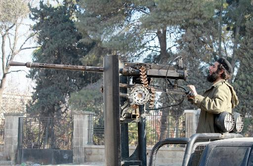 A rebel fighter aims his heavy machine gun mounted on the back of a pick-up truck outside the headquarters of the Islamic State of Iraq and the Levant (ISIL) in Aleppo, northern Syria, on January 8, 2014