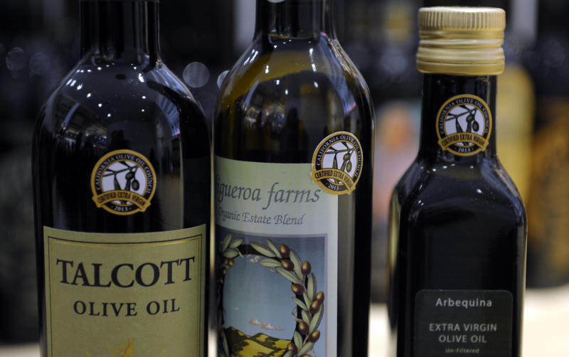 "This photo taken Feb. 14, 2014 shows dertification stickers are affixed to bottles of California olive oil displayed and for sale at the All Things Olive shop in Washington. It's a pressing matter for the tiny U.S olive oil industry. Shoppers are more often pouring European oil _ it's cheaper and viewed as more authentic than the American competition. And that's pitting U.S. producers against importers of the European oil. Some liken the battle to the California wine industry's struggles to gain acceptance decades ago. The tiny California olive industry says European olive oil filling U.S. shelves often is mislabeled and lower grade. They're pushing the federal government to give more scrutiny to imported varieties. One congressman-farmer even goes as far as suggesting labels on imported oil say ""extra rancid"" rather than extra virgin. Stricter standards might help American producers grab more market share from the dominant Europeans. (AP Photo/Susan Walsh)"