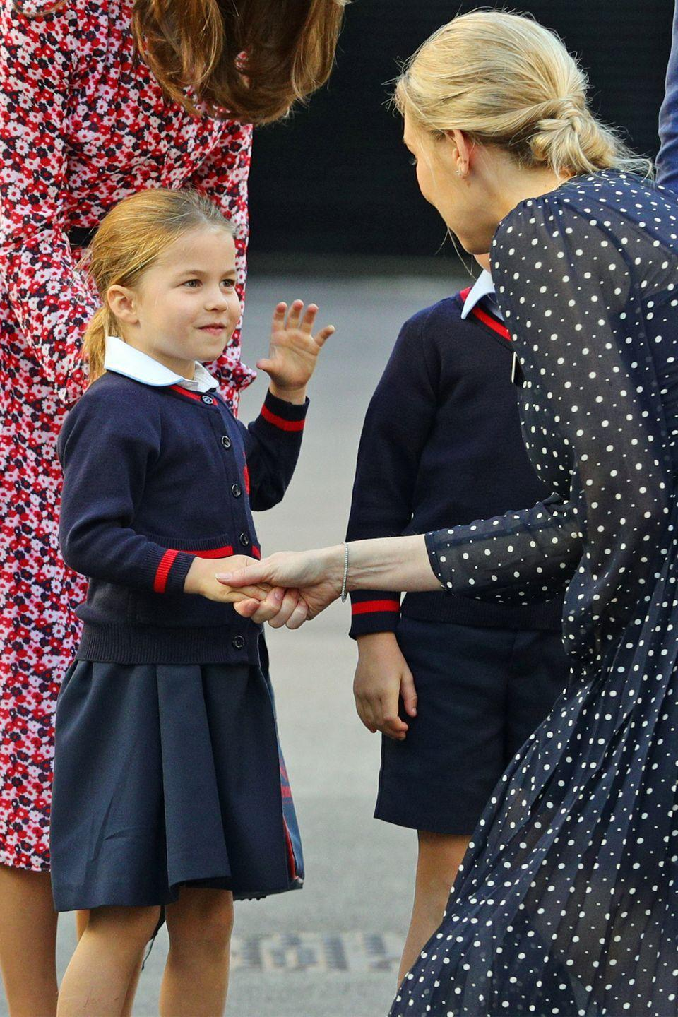 <p>Princess Charlotte shakes hands with a staff member from Thomas's Battersea.</p>