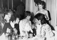 <p>At a party thrown by David Bowie at the Cafe Royal in 1973. (L to R) Lou Reed, Mick Jagger and David Bowie. Standing is Lulu.</p>