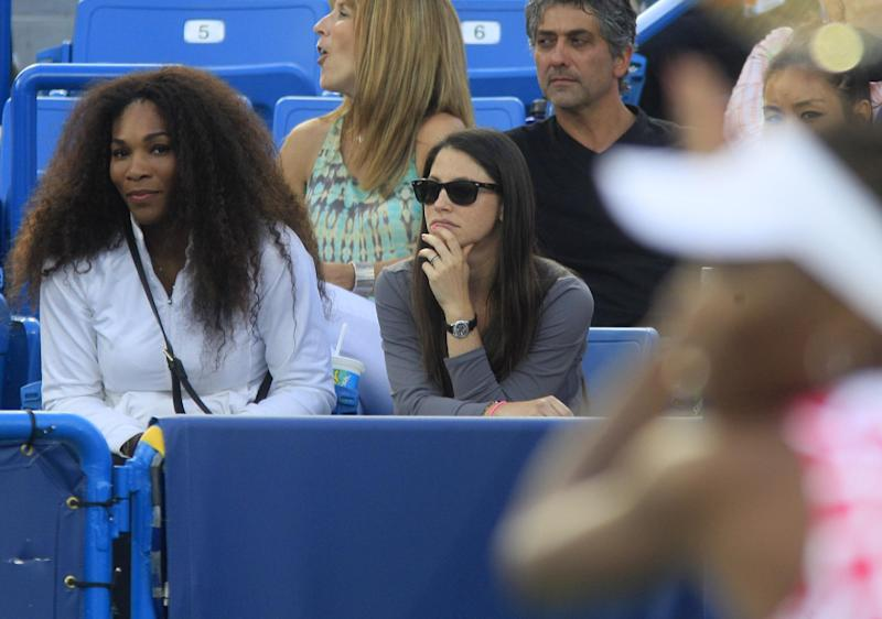 Serena Williams, left, watches her sister Venus Williams, right, play in a semifinals match against Li Na, from China, at the Western & Southern Open tennis tournament, Saturday, Aug. 18, 2012, in Mason, Ohio. (AP Photo/Al Behrman)
