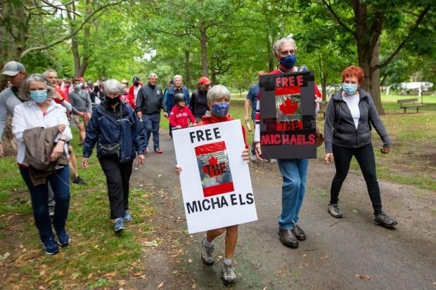 Supporters of Michael Kovrig and Michael Spavor take part in a march in Ottawa on Sept. 5, 2021, marking 1,000 days since the two men were detained in China on charges of espionage. (Lars Hagberg/AFP/Getty Images - image credit)
