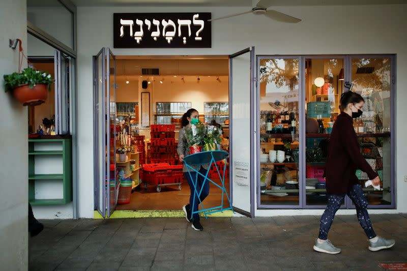 An employee carries a table at a cafe as Israel further eases the coronavirus disease (COVID-19) restrictions in Tel Aviv