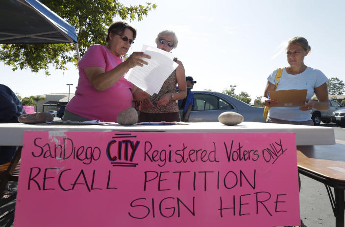 Cecelia Taylor, left, explains a form to Tana Piontek, center, as Allie Thornbrue, right, waits to sign a petition to recall San Diego Mayor Bob Filner at a stand set up in the parking lot of a shopping center Wednesday, Aug. 21, 2013, in San Diego. Pressure is mounting against San Diego's mayor to resign after a sexual harassment lawsuit was filed against him, and the Democratic National Committee plans to vote on a resolution Friday urging him to step down immediately. (AP Photo/Gregory Bull)