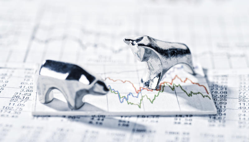 Two small silver figurines of a bull and a bear facing each other on top of a sheet with a stock symbols and a stock price chart.