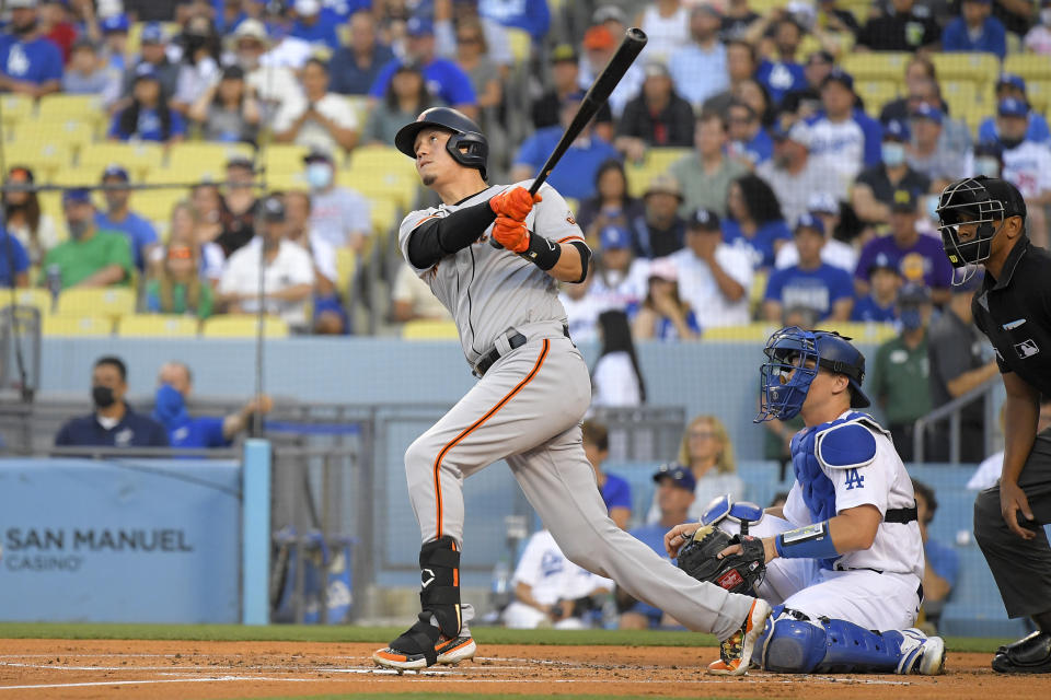 San Francisco Giants' Wilmer Flores, left, hits a solo home run as Los Angeles Dodgers catcher Will Smith, center, watches along with home plate umpire Jeremie Rehak during the first inning of a baseball game Monday, July 19, 2021, in Los Angeles. (AP Photo/Mark J. Terrill)