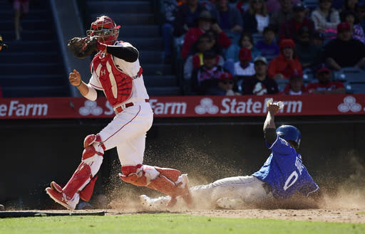 Kansas City Royals' Terrance Gore, right, is forced out at home by Los Angeles Angels catcher Kevan Smith, left, during the ninth inning of a baseball game Sunday, May 19, 2019, in Anaheim, Calif. (AP Photo/Mark J. Terrill)
