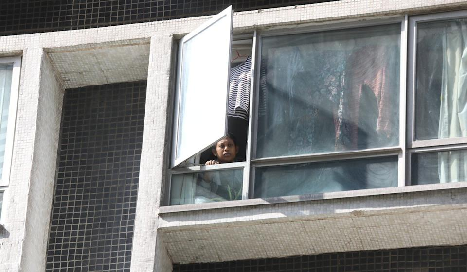 A resident peers out a window at the private housing estate. Photo: K.Y. Cheng