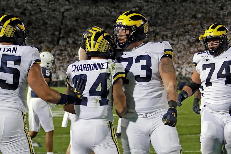 Michigan running back Zach Charbonnet celebrates his touchdown with Jalen Mayfield (73) during the first half against Penn State in State College, Pa., Saturday, Oct. 19, 2019.