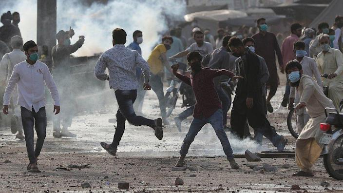 Supporters of the Islamic party Tehreek-e-Labbaik Pakistan (TLP) throw stones at police during a protest demanding the release of their leader Saad Hussain Rizvi