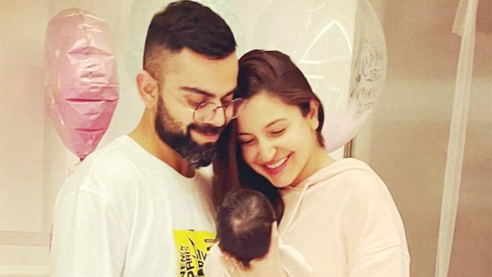 Virat Kohli (pictured left) smiles with wife Anushka Sharma (pictured right) holding newborn baby Vamika.