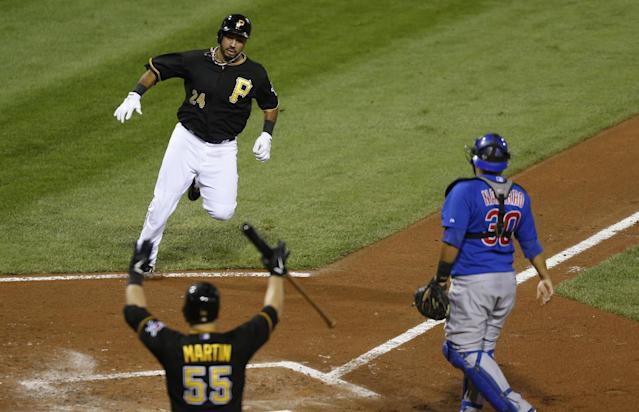 Pittsburgh Pirates' Pedro Alvarez, top left, is cheered by on-deck batter Russell Martin (55) while heading to home plate with an inside-the park home run as Chicago Cubs catcher Dioner Navarro awaits a throw in the fourth inning of a baseball game on Friday, Sept. 13, 2013, in Pittsburgh. (AP Photo/Keith Srakocic)