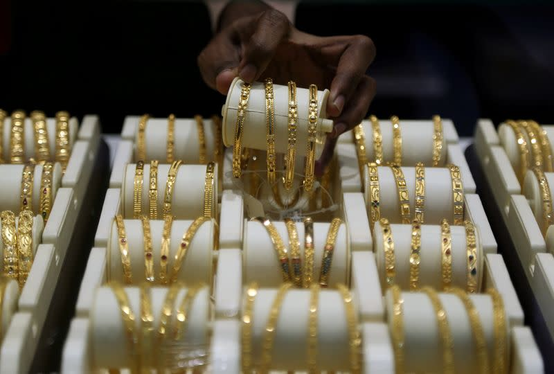 FILE PHOTO: A salesman arranges gold bangles inside a jewellery showroom on the occasion of Akshaya Tritiya, a major gold buying festival, in Mumbai