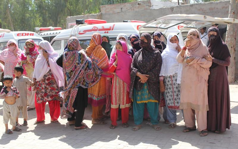 Relatives wait to receive bodies of the victims after a custodian of a local shrine in Sargodha allegedly killed at least 20 disciples - EPA
