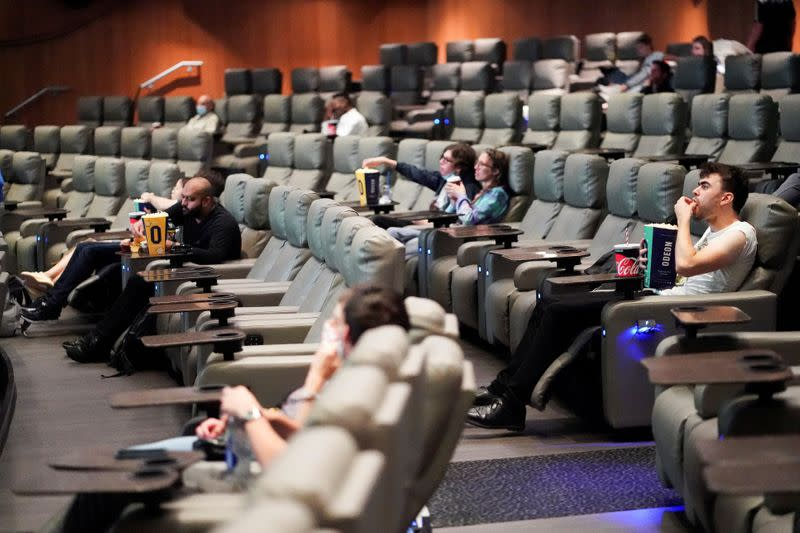 """FILE PHOTO: People take their seats inside the Odeon Luxe Leicester Square cinema, on the opening day of the film """"Tenet"""", in London"""