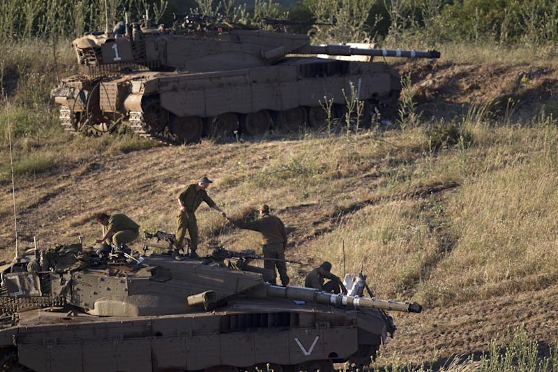 "Israeli soldiers work on top of a tank in a position in the Israeli controlled Golan Heights, on the border with Syria, Tuesday, May 21, 2013. Israel's military chief has issued a stern warning to Syrian leader Bashar Assad after an Israeli military jeep came under fire from Syrian forces early Tuesday. Lt. Gen. Benny Gantz said Tuesday that Israel will not allow the Golan Heights ""to become a comfortable sphere for Assad to operate from."" He said that if the situation deteriorates further, Assad ""will have to bear the consequences."" (AP Photo/Ariel Schalit)"