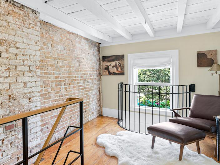 A room with exposed brick with stairs leading up to a sitting area with a window in the back
