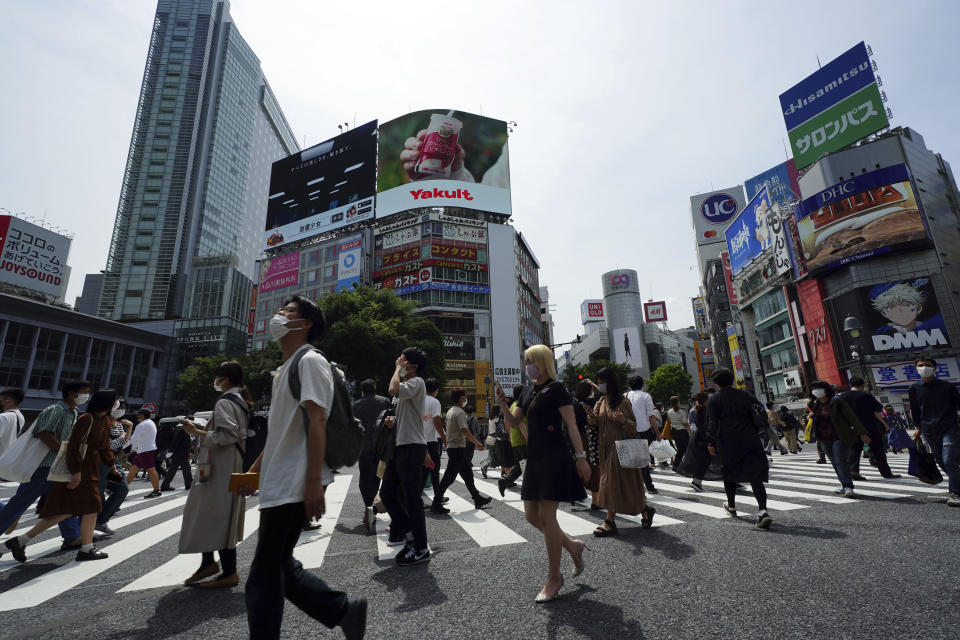 People wearing protective masks to help curb the spread of the coronavirus walk along a pedestrian crossing Friday, May 14, 2021, in Tokyo. The Japanese capital confirmed more than 850 new coronavirus cases on Friday. (AP Photo/Eugene Hoshiko)