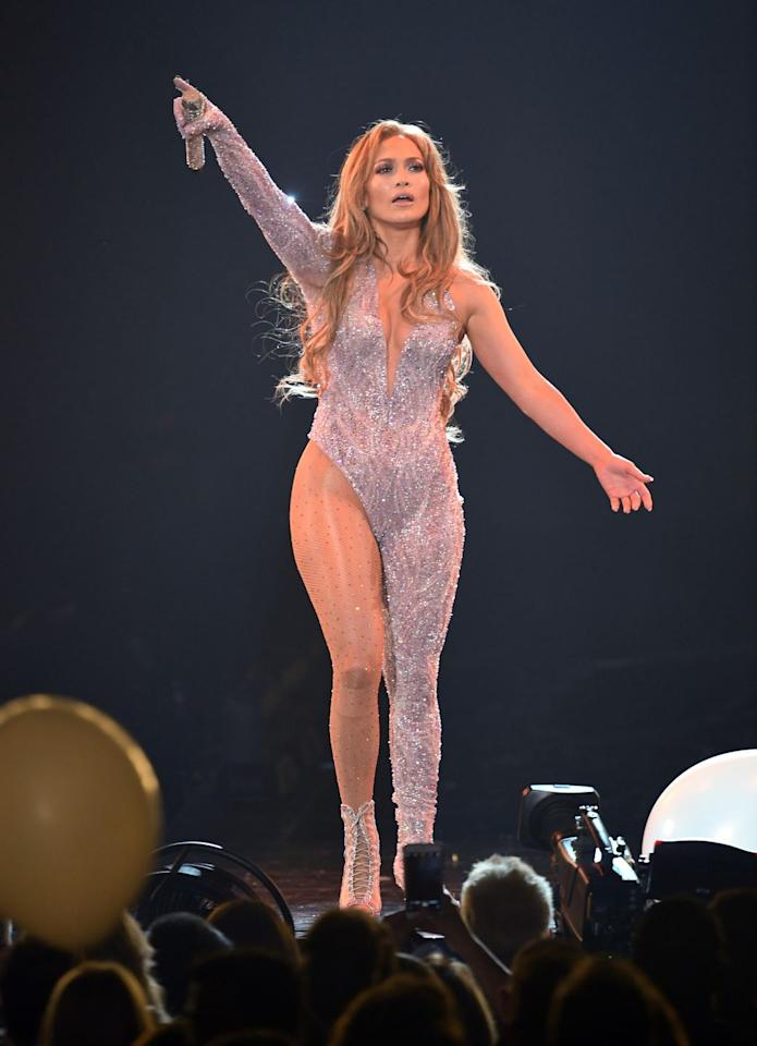 """<p>During her <em><a href=""""https://www.oprahmag.com/entertainment/a26323203/jennifer-lopez-2019-birthday-tour/"""" target=""""_blank"""">It's My Party</a></em><em></em> tour stop in Los Angeles, Lopez stepped onto the stage in this one-legged Versace jumpsuit, covered in Swarovski crystals and matching dance booties by Burju<em>. </em></p>"""