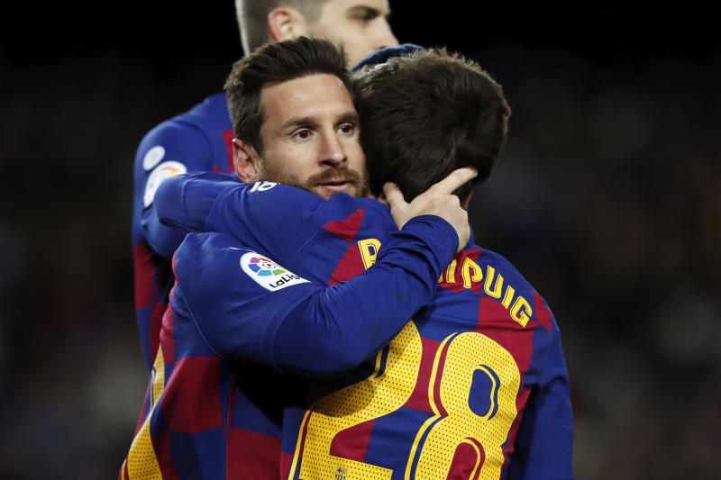 Barcelona's Lionel Messi, left, celebrates with Ricard Puig, right, after scoring the opening goal during a Spanish La Liga soccer match between Barcelona and Granada at Camp Nou stadium in Barcelona, Spain, Sunday, Jan. 19, 2020. (AP Photo/Joan Monfort)