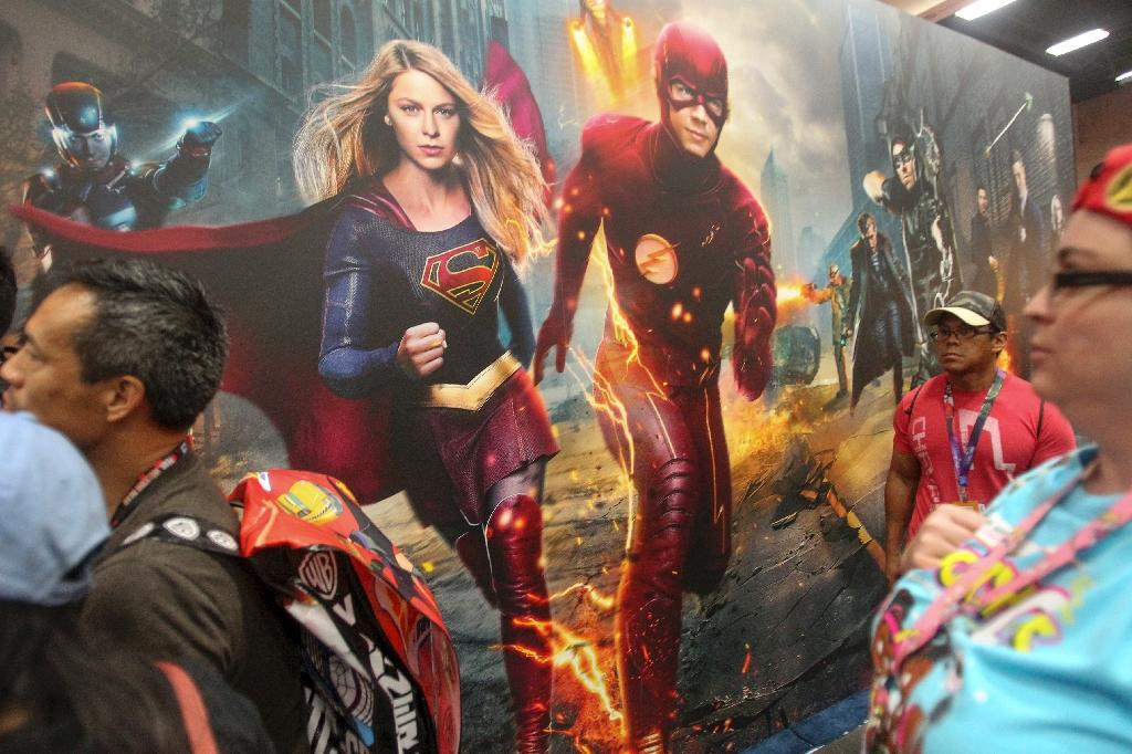 Convention-goers saunter by as Supergirl and The Flash jump pff a mural during Comic-Con International 2016 in San Diego, California on July 21, 2016 (AFP Photo/Bill Wechter)