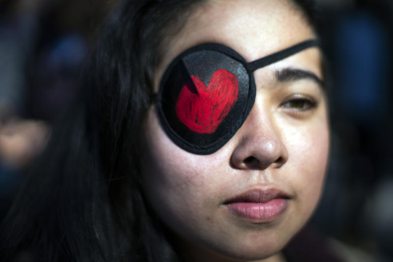 A woman covers her eye in solidarity with the Chilean protestors as people participate in a rally celebrating International Women's Day at Washington Square Park in New York, Sunday, March 8, 2020.(AP Photo/Eduardo Munoz Alvarez)