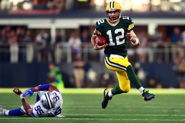 Aaron Rodgers of the Green Bay Packers scrambles with the ball against David Irving of the Dallas Cowboys in the fourth quarter, at AT&T Stadium in Arlington, Texas, on October 8, 2017 (AFP Photo/TOM PENNINGTON)