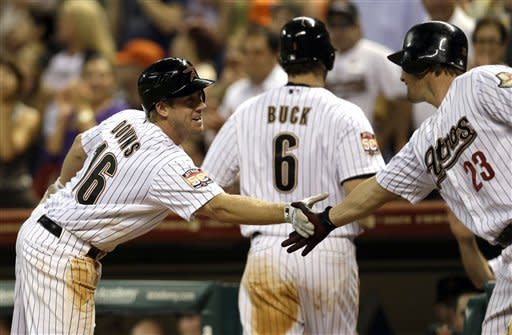 Houston Astros' Matt Downs (16) is congratulated by teammate Chris Johnson (23) after hitting a two-run home run against the New York Mets during the sixth inning of a baseball game Monday, April 30, 2012, in Houston. The Astros' Travis Buck scored on Downs' homer. (AP Photo/David J. Phillip)