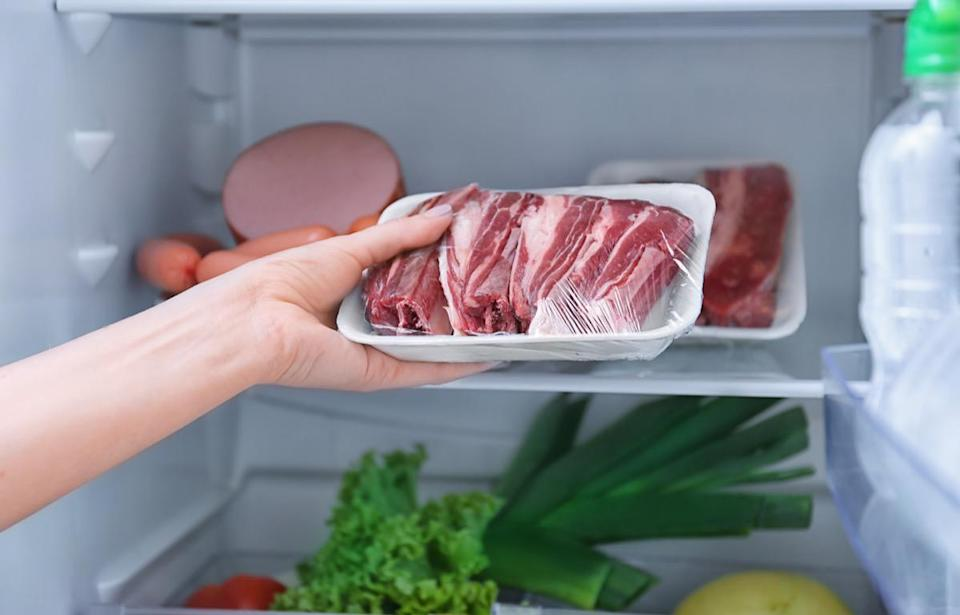 Woman putting raw meat in refrigerator