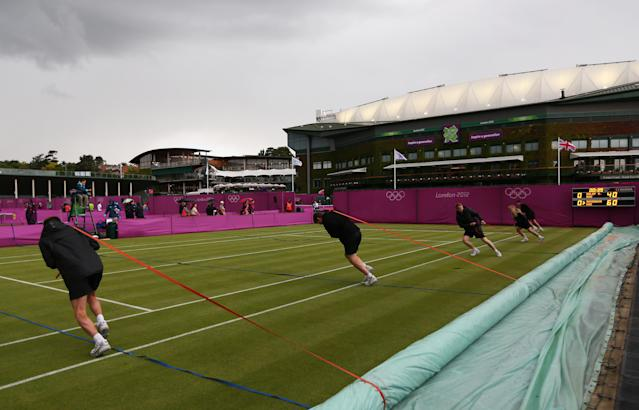 LONDON, ENGLAND - JULY 29: Members of the ground staff pull the rain covers across the court as rain delays play on Day 2 of the London 2012 Olympic Games at the All England Lawn Tennis and Croquet Club in Wimbledon on July 29, 2012 in London, England. (Photo by Clive Brunskill/Getty Images)