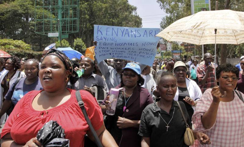 FILE- In this file photo of Friday, March 9, 2012, Kenyan health workers demonstrate in the streets of Nairobi, Kenya. Doctors in Kenya's public hospitals on Wednesday Oct. 3, 2012 spent their 17th day on strike to protest the dilapidated state of public health care. Emergency rooms in some of Kenya's public hospitals frequently don't have gloves or medicine, and power outages sometimes force doctors to use the light from their phones to complete a procedure. Kenya's government fired 1,000 of the 2,000 striking doctors last week despite a shortfall of skilled medical practitioners. (AP Photo/ Khalil Senosi-File)