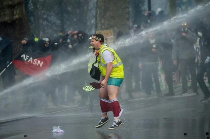 A 'Yellow Vest' protester is soaked by a police water cannon (AFP Photo/Loic VENANCE)